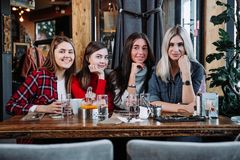4 друз в кафе смотрят камеру и смеются над Стоковая Фотография