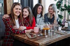 4 друз в кафе смотрят камеру и смеются над Стоковое Изображение RF