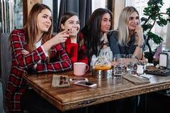 4 друз в кафе смотрят камеру и смеются над Стоковые Фотографии RF