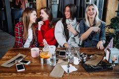 4 друз в кафе смотрят камеру и смеются над Стоковое Фото