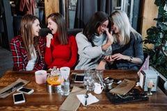 4 друз в кафе смотрят камеру и смеются над Стоковые Изображения RF