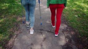 2 друз в парке, один со сломанной ногой и костыли сток-видео