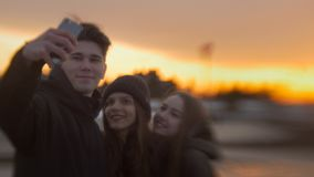 3 друз делая selfie для прогулки на заходе солнца Стоковое фото RF
