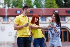 3 друз есть мороженое, шутящ, имеющ потеху Стоковое Изображение