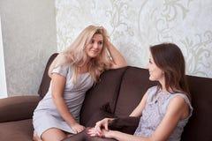 2 друз женщин беседуя на кресле дома Стоковое Изображение RF