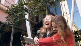 2 друз женщин используя цифровой планшет в outdoors Усмехаясь подруги рассматривая фото на приборе планшета, идя сток-видео