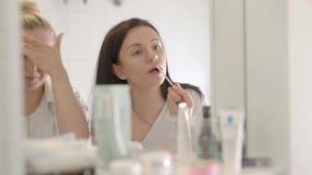 2 друз идут к партии Молодые женщины положили макияж на bathroom акции видеоматериалы