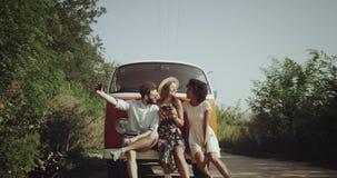 3 друз, имеющ славное время совместно нося ретро стильные одежды, около оранжевой винтажной шины около дороги акции видеоматериалы
