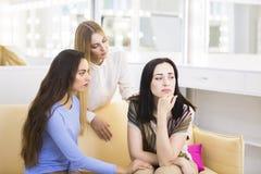 2 друз и унылой женщина youg siiting на софе Стоковые Изображения
