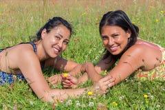 2 друз лежа совместно в зеленой траве стоковая фотография