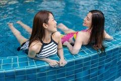 2 друз молодых женщин наслаждаются в бассейне Стоковое Изображение