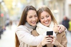 2 друз наблюдая умное содержание телефона в зиме Стоковое фото RF