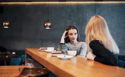 2 друз наслаждаясь кофе совместно в кофейне по мере того как они сидят на беседовать таблицы Стоковая Фотография