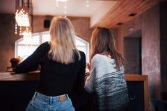 2 друз наслаждаясь кофе совместно в кофейне по мере того как они сидят на беседовать таблицы Стоковое фото RF