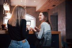 2 друз наслаждаясь кофе совместно в кофейне по мере того как они сидят на беседовать таблицы Стоковое Фото