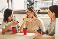 3 друз наслаждаясь чашкой кофе на кафе Стоковая Фотография RF