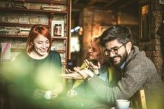 3 друз на кафе играя игру Стоковое фото RF