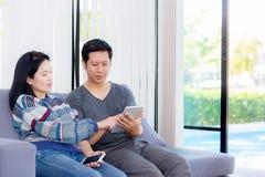 2 друз на линии с множественными приборами и говоря сидеть на софе в живущей комнате Стоковое фото RF