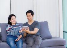 2 друз на линии с множественными приборами и говоря сидеть на софе в живущей комнате в интерьере дома Стоковое Фото