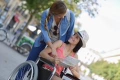 2 друз посещая чужой город один сидя в кресло-коляске стоковая фотография rf