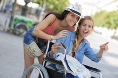 2 друз посещая чужой город один сидя в кресло-коляске стоковое изображение rf