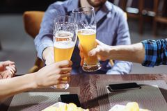3 друз провозглашать с стеклами светлого пива на пабе Стоковые Изображения RF