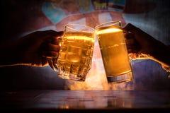 2 друз провозглашать (clinking) с стеклами светлого пива на пабе Красивая предпосылка с запачканным взглядом флага Хорватии Стоковая Фотография