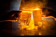 2 друз провозглашать (clinking) с стеклами светлого пива на пабе Красивая предпосылка с запачканным взглядом флага Дании Стоковые Изображения