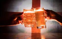 2 друз провозглашать (clinking) с стеклами светлого пива на пабе Красивая предпосылка с запачканным взглядом флага Англии Стоковые Фотографии RF