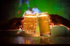 2 друз провозглашать (clinking) с стеклами светлого пива на пабе Красивая предпосылка с запачканным взглядом играть игру на t Стоковое фото RF