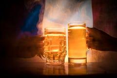 2 друз провозглашать (clinking) с стеклами светлого пива на пабе Красивая предпосылка с запачканным взглядом флага Франции S Стоковая Фотография RF