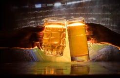 2 друз провозглашать (clinking) с стеклами светлого пива на пабе Красивая предпосылка с запачканным взглядом играть игру на t Стоковые Изображения RF