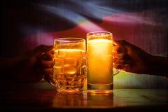 2 друз провозглашать (clinking) с стеклами светлого пива на пабе Красивая предпосылка с запачканным взглядом флага Германии Стоковые Изображения RF