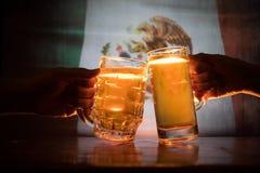 2 друз провозглашать (clinking) с стеклами светлого пива на пабе Красивая предпосылка с запачканным взглядом флага Мексики S Стоковые Фото