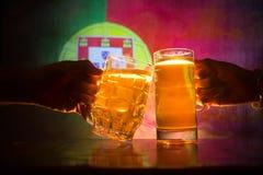 2 друз провозглашать (clinking) с стеклами светлого пива на пабе Красивая предпосылка с запачканным взглядом флага Португалии Стоковая Фотография