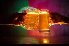 2 друз провозглашать (clinking) с стеклами светлого пива на пабе Красивая предпосылка с запачканным взглядом флага Португалии Стоковые Фото