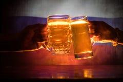2 друз провозглашать (clinking) с стеклами светлого пива на пабе Красивая предпосылка с запачканным взглядом флага России S Стоковое Изображение RF
