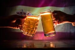 2 друз провозглашать (clinking) с стеклами светлого пива на пабе Красивая предпосылка с запачканным взглядом флага Испании Su Стоковые Изображения
