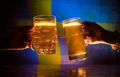 2 друз провозглашать (clinking) с стеклами светлого пива на пабе Красивая предпосылка с запачканным взглядом флага Швеции S Стоковое Изображение RF