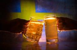 2 друз провозглашать (clinking) с стеклами светлого пива на пабе Красивая предпосылка с запачканным взглядом флага Швеции S Стоковая Фотография RF