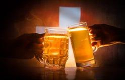2 друз провозглашать (clinking) с стеклами светлого пива на пабе Красивая предпосылка с запачканным взглядом флага Switzerla Стоковое Фото