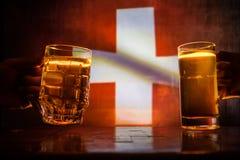 2 друз провозглашать (clinking) с стеклами светлого пива на пабе Красивая предпосылка с запачканным взглядом флага Switzerla Стоковые Изображения