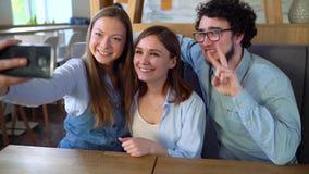 3 друз сидят в кафе, имеют потеху связывая и делают selfie движение медленное сток-видео