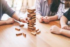3 друз сидя и играя игра блока башни падения деревянная совместно стоковое фото