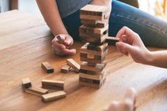 3 друз сидя и играя игра блока башни падения деревянная совместно стоковое изображение rf