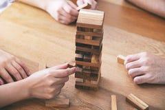 3 друз сидя и играя игра блока башни падения деревянная совместно стоковые фотографии rf