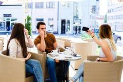 3 друз сидя на кафе пока одно из их bussy путем принимать selfie Стоковое Изображение
