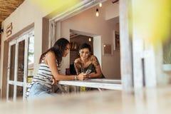 2 друз смотря мобильный телефон сидя на таблице Стоковая Фотография RF