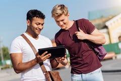 2 друз смотря современную таблетку Стоковое фото RF
