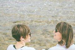 2 друз усмехаясь и смотря один другого морем Социальная фотография стиля сети Стоковое Изображение RF